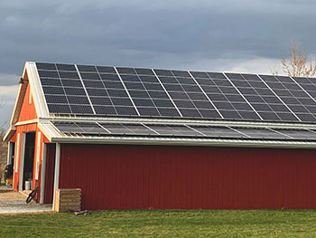 Red barn with solar panels on the roof.