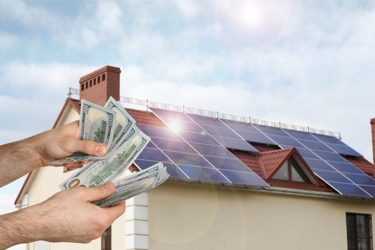 man counting money against a building with installed solar panels on roof.